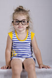 Two-year-old girl in funny glasses sitting looking in the frame. Portrait Stock Image