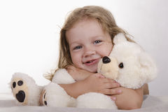 Two-year-old girl lies and bear hugs Stock Image