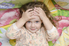 Two-year-old girl lying on the bed and his head in his hands, looks fun in the frame Stock Photo