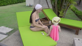 Two-year-old girl near hotel pool. Two-year-old girl with her mother near the resort`s pool stock video