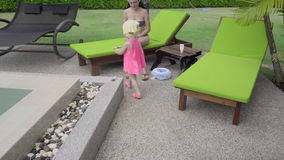 Two-year-old girl near hotel pool. Two-year-old girl with her mother near the resort`s pool stock video footage