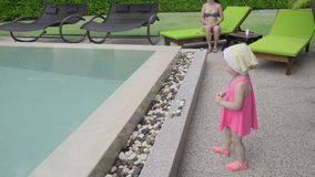 Two-year-old girl near hotel pool. Two-year-old girl with her mother near the resort`s pool stock footage