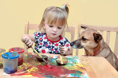 Two year old girl painting. A two year old little girl, painting at the table, with her dog sitting next to her Stock Photos