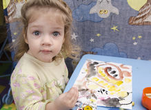 Two-year-old girl is painting at the table and looks in a frame Royalty Free Stock Photography