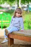 Two year old girl on  park bench Stock Photo