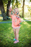 Two-year old girl stained in colors against green lawn. Two-year old girls stained in colors against green lawn Royalty Free Stock Photography