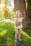 Two-year old girl stained in colors against green lawn. Two-year old girls stained in colors against green lawn Stock Images
