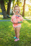 Two-year old girl stained in colors against green lawn. Two-year old girls stained in colors against green lawn Royalty Free Stock Photos