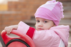 Two-year-old girl thoughtfully looks sitting on a bike Royalty Free Stock Photos