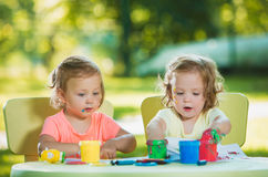 Two-year old girls painting with poster paintings together against green lawn Royalty Free Stock Image