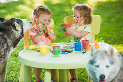 Two-year old girls painting with poster paintings together against green lawn Royalty Free Stock Photography