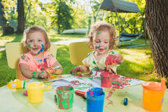 Two-year old girls painting with poster paintings together against green lawn. Two-year old girls painting with poster paintings and sitting at a table together Royalty Free Stock Images