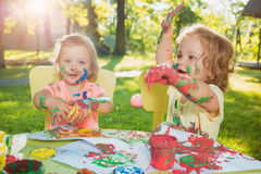 Two-year old girls painting with poster paintings together against green lawn Stock Image