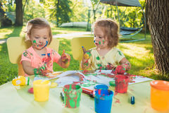 Two-year old girls painting with poster paintings together against green lawn Stock Images
