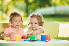 Two-year old girls painting with poster paintings together against green lawn Stock Photos