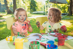 Two-year old girls painting with poster paintings together against green lawn Royalty Free Stock Images