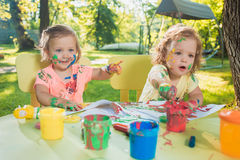 Two-year old girls painting with poster paintings together against green lawn Royalty Free Stock Photo