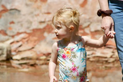 A Two Year Old Holds Hands with Mommy. This two-year-old pixie holds hands with mommy down at the creek Royalty Free Stock Images