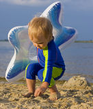 Two-year-old kid playing near water Royalty Free Stock Photos