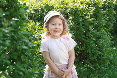 Two year-old laughing girl in corduroy flat cap at green garden shrubbery background Stock Photography