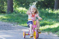 Two year-old laughing girl wearing corduroy flat cap and polka-dotted costume cycling kids pink and yellow tricycle Royalty Free Stock Photography