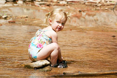 A Two Year Old Pixie at the Creek. This two-year-old pixie just loves playing in her new swimsuit down at the creek Royalty Free Stock Photography