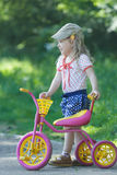 Two year-old standing near pink and yellow kids tricycle with steel frame Stock Photography