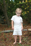Two year old standing in a wooded area Royalty Free Stock Images