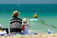 Two year old toddler boy with mother on beach. Two year old toddler boy in sun hat with mother on beach Royalty Free Stock Image