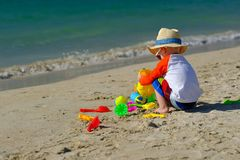 Two year old toddler playing on beach. Two year old toddler boy playing with beach toys on beach Royalty Free Stock Photography