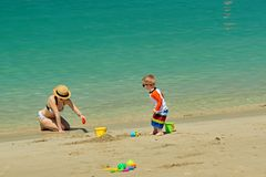 Two year old toddler playing with mother on beach. Two year old toddler boy playing with beach toys with mother on beach Stock Photos