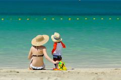 Two year old toddler playing with mother on beach. Two year old toddler boy playing with beach toys with mother on beach Royalty Free Stock Photo
