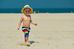Two year old toddler boy running on beach. Two year old toddler boy in sun hat running on beach Royalty Free Stock Images