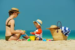 Toddler boy playing with mother on beach. Two year old toddler boy in sun hat playing with mother on beach Stock Photography
