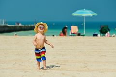 Two year old toddler boy running on beach. Two year old toddler boy in sun hat running on beach Stock Images