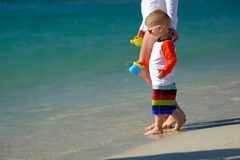 Two year old toddler walking on beach with mother Stock Image