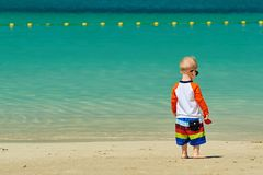 Two year old toddler boy walking on beach. Two year old toddler boy in sunglasses walking on beach Royalty Free Stock Image