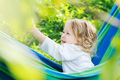 Two year-old toddler girl is laughing and playing in striped blue-green Brazilian hammock Royalty Free Stock Photos