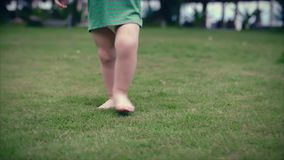 Two-year-old toddler little boy walks on the summer of on the green grass. Slow motion. Clouse up. Two-year-old toddler little boy walks on the summer of on the
