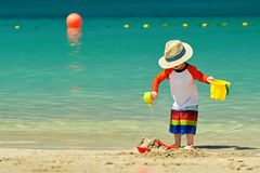 Two year old toddler playing on beach. Two year old toddler boy playing with beach toys on beach Stock Photo