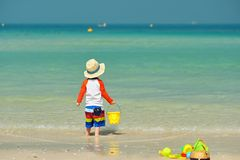 Two year old toddler playing on beach. Two year old toddler boy playing with beach toys on beach Royalty Free Stock Image