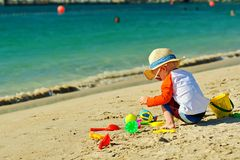 Two year old toddler playing on beach. Two year old toddler boy playing with beach toys on beach Royalty Free Stock Photos