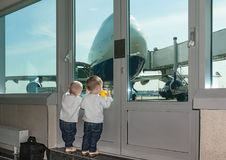 Two-year-old twins wait at airport. royalty free stock photos