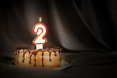 Two years anniversary. Birthday chocolate cake with white burning candle in the form of number Two. Dark background with black cloth royalty free stock photography