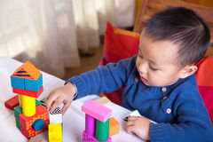 Two years boy playing with wooden blocks. Royalty Free Stock Photos