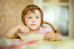 Two-years child eats from plate Stock Photos