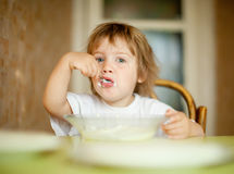 Two-years child  eats from plate Royalty Free Stock Photo