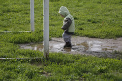 Two years child walk and playing in muddy puddle Royalty Free Stock Image