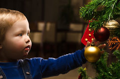 Two years old boy decorating a Christmas tree Stock Images