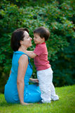 Two years old boy hugs his young mom in park. Cute two years old boy hugs his young mom in park royalty free stock photography